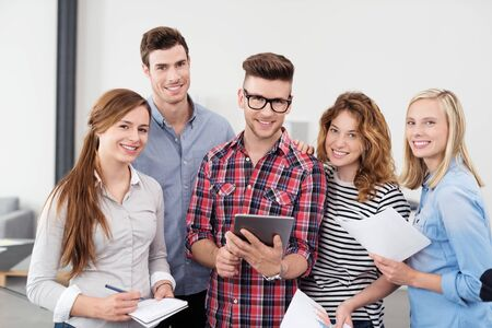 holding notes: Five Cheerful Young Office Workers in Casual Clothing, Holding Notes and Tablet Computer and Smiling at the Camera.