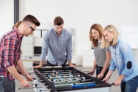 Cinque giovani ufficio persone che godono di Calcio Balilla gioco durante il loro tempo libero al posto di lavoro.