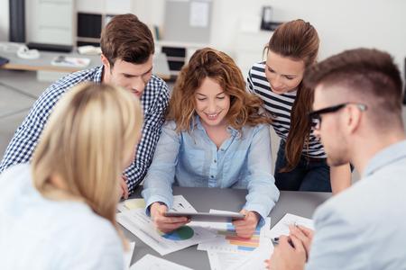 タブレット コンピューターを一緒に見て 5 つの若いオフィスの人々 中ビジネスを持つ会議室中会議します。