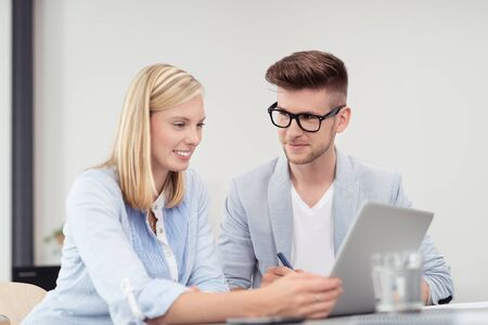 staff training: Young Business Couple Discussing Something at the Table with Laptop Computer Inside the Office. Stock Photo