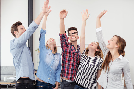 achievement: Group of Five Happy Young Office Worker with Hands in the Air Hoping for Success on their Plans. Stock Photo