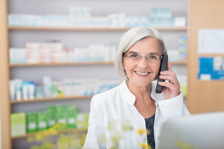 pharmacist: Happy smiling elderly female pharmacist talking on a telephone as she stands behind the counter in the pharmacy assisting a client