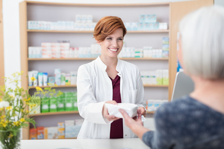 adult care: Smiling attractive young redhead pharmacist handing over prescribed medicines to an elderly female patient, view over the clients shoulder of the pharmacist Stock Photo