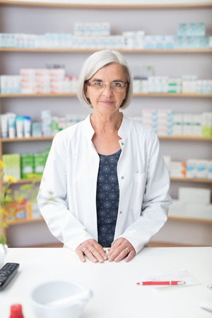 stocked: Senior female pharmacist in her pharmacy standing behind the counter in her white lab coat looking at the camera, stocked shelves behind