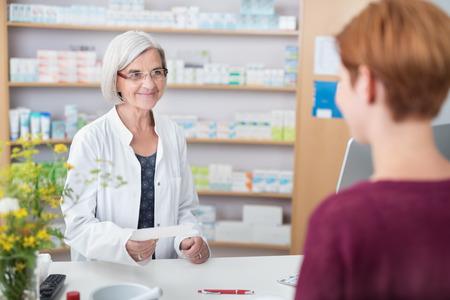 Vriendelijke vrouwelijke apotheker die achter haar toonbank bij de apotheek te helpen een cliënt met een artsenvoorschrift