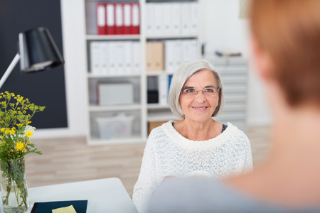gray haired: Gray Haired Senior Businesswoman Listening to her Subordinate Talking to her with Happy Facial Expression. Stock Photo