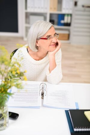 Elderly businesswoman sitting at her desk in the office watching something with her chin resting on her hand and a smile on her face, looking to the right side of the frame