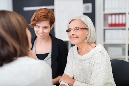 candidato di lavoro femminile con gli ufficiali di due donne del personale dando loro una presentazione sulle sue qualifiche mentre ascoltano con attenzione Archivio Fotografico