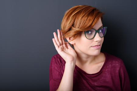 drum: Young woman with a hearing disorder or hearing loss cupping her hand behind her ear with her head turned aside to try and amplify and channel the available sound to her ear drum Stock Photo