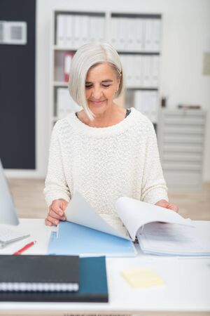 Stylish senior businesswoman in the office standing at a table paging through a large file of paperwork, upper body view