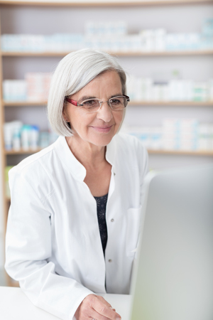 stocked: Elderly lady pharmacist working at a computer in the pharmacy checking information smiling as she works, close up view with stocked shelves behind