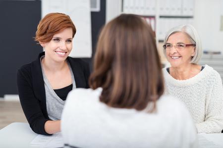 job: Dos Mujeres Felices oficina escuchando a su Manager en su tabla de hablar con ellos.