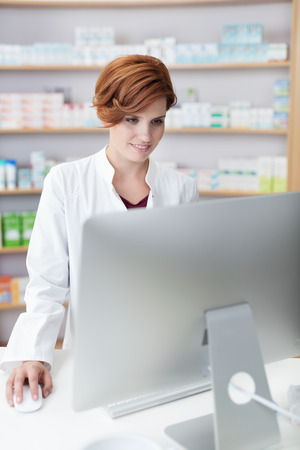 Attractive female pharmacist checking information standing reading a large computer monitor on her desk in the pharmacy Stock Photo