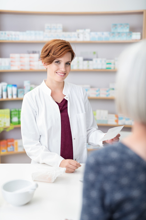 stocked: Smiling pretty pharmacist in a drugstore holding a prescription fro medicine brought in by an elderly lady, stocked shelves in the background