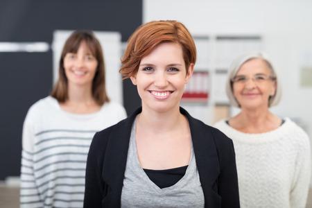 vejez feliz: Mujer Bonita Oficina joven que sonríe en la cámara contra sus dos colegas femeninos