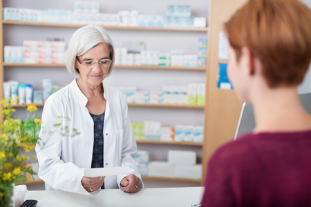 pharmacist: Senior lady pharmacist assisting a patient with prescription medication standing behind the counter reading the script Stock Photo