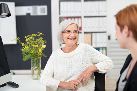 gray haired: Gray Haired Middle Aged Office Woman Listening to her Young Colleague Talking to Her Inside the Office.