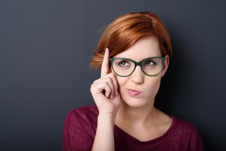 Nerdy jeune femme portant des lunettes de geek scolastique pensée avec son doigt levé et une grimace de concentration dans une représentation stéréotypée humour debout, sur un fond foncé avec copyspace