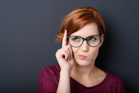 women: Nerdy scholastic young woman wearing geeky glasses standing thinking with her finger raised and a grimace of concentration in a humorous stereotypical depiction, over a dark background with copyspace