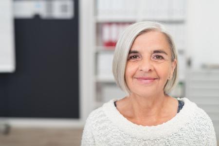 Close-up Gray Haired Midden Oude vrouw lachend op de camera binnen het kantoor.