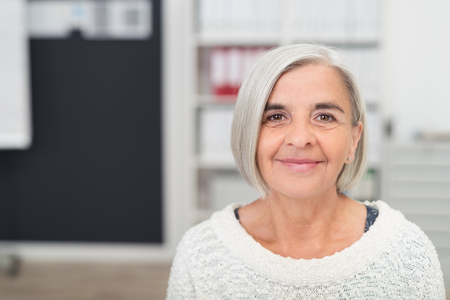 smiling: Close up Gray Haired Middle Aged Woman Smiling at the Camera Inside the Office. Stock Photo