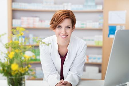 El farmacéutico confiado feliz joven de la mujer joven que se inclina en un escritorio en la farmacia que da a la cámara una sonrisa amistosa caliente grande preciosa