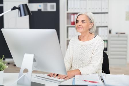 vejez feliz: Superior de la empresaria en el trabajo en la oficina sentado en su escritorio escribiendo en la información de la computadora de escritorio Foto de archivo