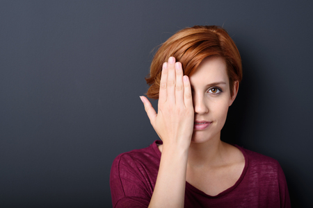 Attractive young redhead woman covering one eye with her hand as she stands against a dark background looking directly at the camera, with copyspace