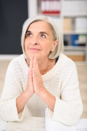 imploring: Fun businesswoman sitting at her desk offering a prayer to heaven as she struggles to find the solution to a problem beseeching God for inspiration