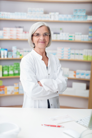 stocked: Confident friendly elderly woman pharmacist standing with folded arms behind the counter smiling at the camera, stocked shelves behind Stock Photo
