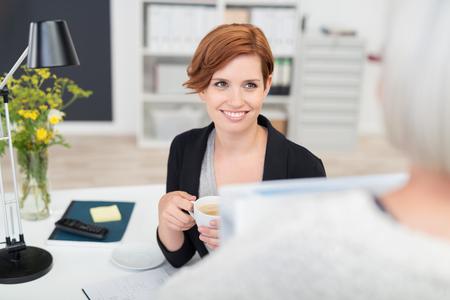 empleado de oficina: Feliz mujer joven de la oficina en su escritorio escucha a su colega hablando con ella durante las vacaciones de tiempo.