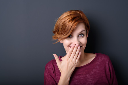 embarrassed: Close up Happy Young Woman Smiling at the Camera While Covering her Mouth with her Hand Against Gray Background with Copy Space.