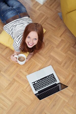 comfortable: High Angle View of a Cheerful Young Woman Holding a Cup of Coffee, Smiling at the Camera. Stock Photo