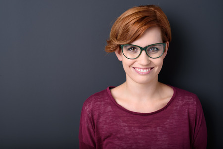 pretty: Pretty woman wearing glasses with a lovely big warm smile standing against a dark background with copyspace, head and shoulders view