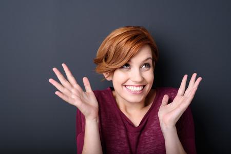 Opgewonden uitbundige mooie jonge vrouw verhogen haar handen in een triomfantelijke gebaar met een stralende glimlach van plezier tijdens het kijken, op een donkere studio achtergrond