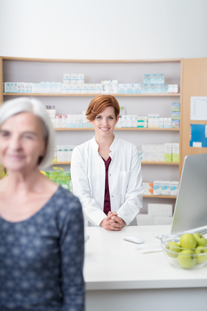 pharmacist: Elderly lady walking away from a smiling friendly attractive young female pharmacist after being served with her medication, focus to the pharmacist