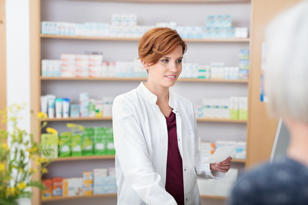 over the counter: Young pretty redhead female pharmacist assisting on older woman with her prescription medication as she smiles at her over the counter