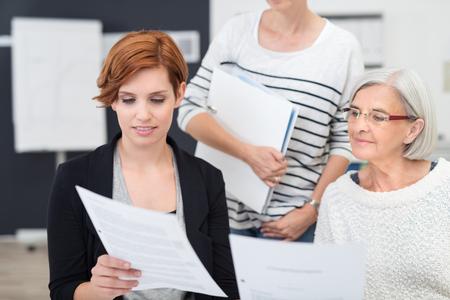 gente exitosa: Tres Oficinistas femenino que lee un documento de negocios juntos en el interior del lugar de trabajo.