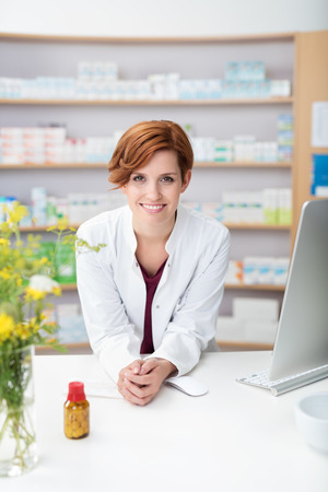 mostradores: Amistoso sonriente mujer joven farmacéutico apoyado en el mostrador de la farmacia con una botella de píldoras en frente de ella sonriendo a la cámara
