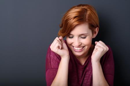 Triumphant jeune femme heureuse célébrant levant les poings à la tête avec un large sourire extatique, la tête et les épaules sur un fond sombre studio Banque d'images - 45610455