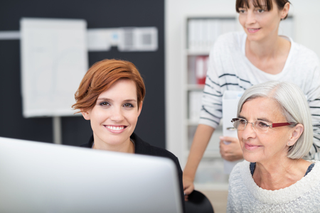 the female: Pretty Young Office Woman Sitting at her Desk with her Two Female Colleagues Next to her Looking at her Computer Screen. Stock Photo