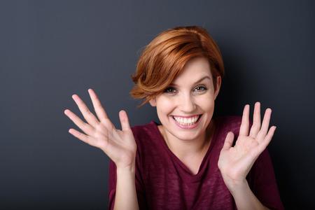 Close-up Vrolijke jonge blonde vrouw lachend op de camera met open handen tegen de grijze muur achtergrond in de studio.