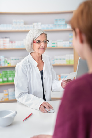 pharmacist: Elderly woman pharmacist processing a prescription for a female customer, over the shoulder view of the pharmacists checking the script on a computer