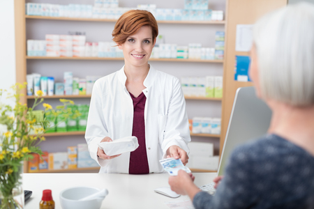 selling service smile: Senior woman patient paying for her medication in a pharmacy handing the pretty smiling female pharmacist a banknote Stock Photo