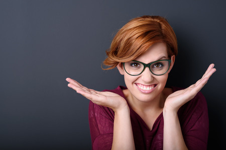persons: Close up Pretty Young Woman Wearing Eyeglasses, Smiling at the Camera with Open Hands Against Gray Wall Background.