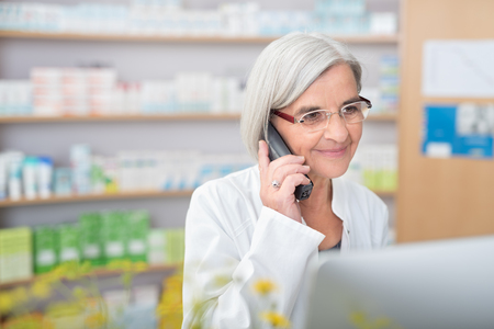phone professional: Pharmacist smiling as she takes a phone call listening to the patient on the line and checking information on her desktop computer as she tries to assist them Stock Photo