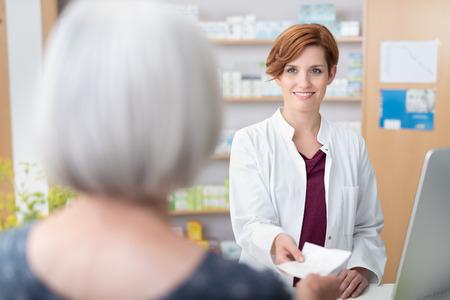 Vrouw patiënt overhandigen de mooie jonge vrouwelijke apotheker een recept over de toonbank, met uitzicht op de lachende apotheker over haar schouder Stockfoto