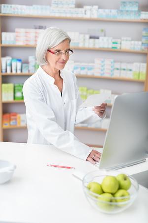 眼鏡とチェック コンピューターの処方薬局で働く白衣のシニア女性薬剤師