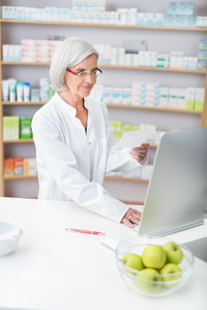 Senior lady pharmacist wearing glasses and a white lab coat working in a pharmacy checking a prescription on the computer Imagens