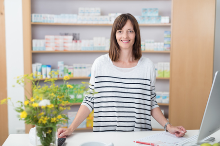 stocked: Smiling pharmacy assistant or pharmacist standing behind a counter in the pharmacy in front of stocked shelves